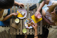 Top view of three young women sitting at wooden table with smoothies and biscuits - MGIF00678