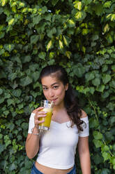 Portrait of smiling young woman drinking a healthy drink - MGIF00684