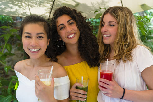 Portrait of three happy young women holding healthy drinks - MGIF00687