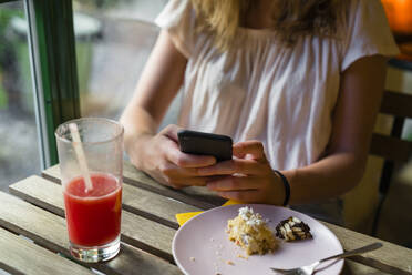 Close-up of young woman sitting at table with a smoothie using cell phone - MGIF00696