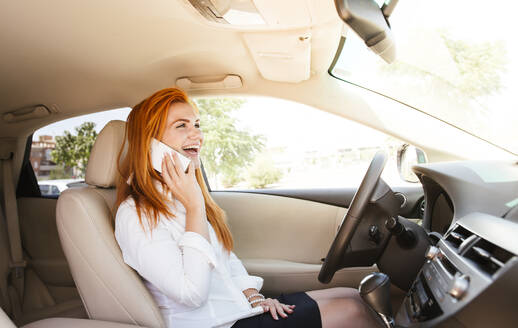 Happy business woman using her smartphone in a car - LJF00701