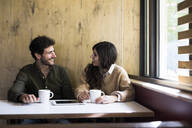 Man and woman talking and drinking coffee in a cafe in Madrid, Spain. - ABZF02427