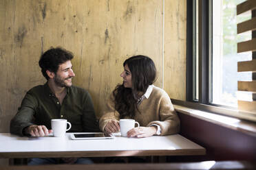 Happy couple drinking coffee in a cafe - ABZF02427
