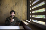 Portrait of a man smiling drinking a coffee and looking at camera in a cafe in Madrid, Spain. - ABZF02430