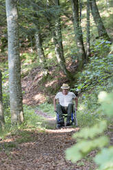 Man in wheelchair in the forest - DRF01749