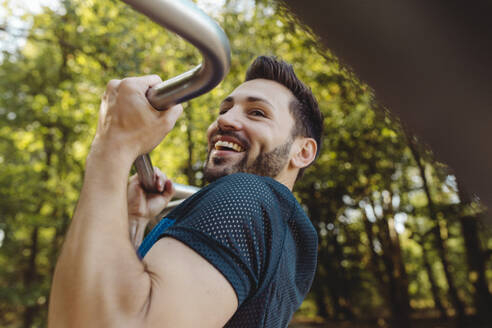 Happy man lifting himself up on a fitness trail - MFF04782