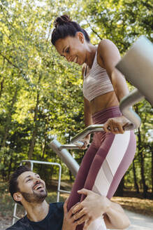 Man supporting woman lifting herself up on a fitness trail - MFF04785