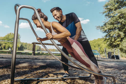 Man supporting woman doing press-ups on a fitness trail - MFF04797