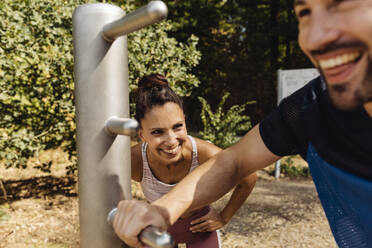 Woman laughing at man stretching on a fitness trail - MFF04833