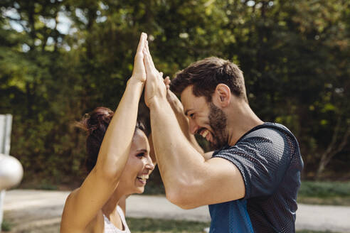 Man and woman high-fiving on a fitness trail - MFF04836