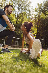 Man and woman stretching on grass near a fitness trail - MFF04839
