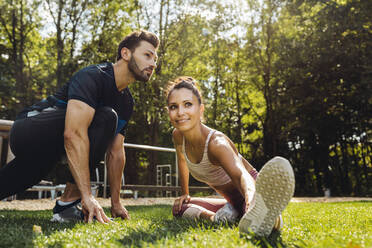 Man and woman stretching on grass near a fitness trail - MFF04842