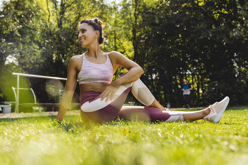 Woman stretching on grass near a fitness trail - MFF04845