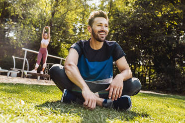 Man sitting on grass near a fitness trail - MFF04851