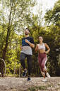 Sporty man and woman running near a fitness trail - MFF04857