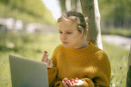 Portrait of young woman with handful of strawberries leaning against tree trunk looking at laptop - KNSF06225
