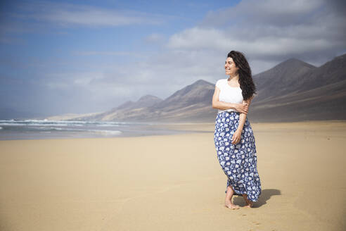 Happy woman standing on the beach looking at distance, Fuerteventura, Spain - ABZF02512
