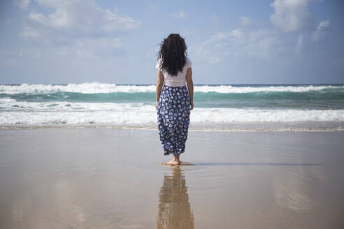 Back view of woman standing on the beach looking at the sea, Fuerteventura, Spain - ABZF02515