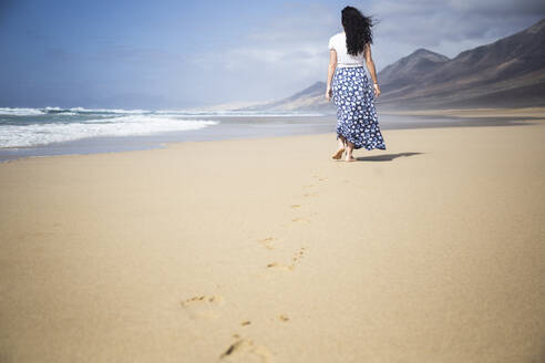 Back view of woman strolling on the beach, Fuerteventura, Spain - ABZF02518