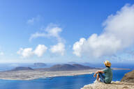 Man on viewpoint looking to La Gracioas island from Lanzarote, Canary Islands, Spain - KIJF02631