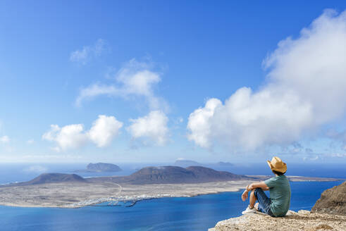 Man on viewpoint looking to La Gracioas island from Lanzarote, Canary Islands, Spain - KIJF02631