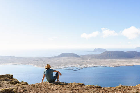Man on viewpoint looking to La Gracioas island from Lanzarote, Canary Islands, Spain - KIJF02634