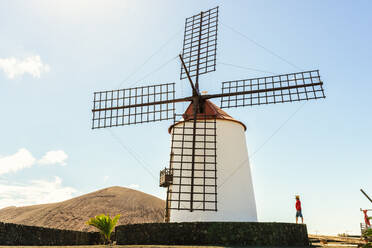 Man next to old windmill, Lanzarote, Canary Islands, Spain - KIJF02637
