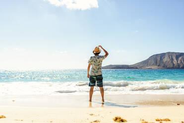 Rear view of man with hat at Playa de las Conchas, Lanzarote, Canary Islands, Spain - KIJF02640