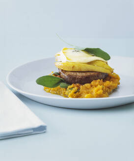 Close-up of beef fillet with pears and Gorgonzola cheese in plate on table - PPXF00262