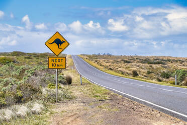 Kangaroo crossing sign by Great Ocean Road against sky, Victoria, Australia - SMAF01314
