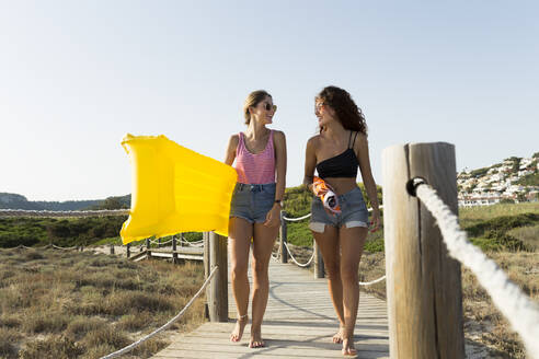 Young women with yellow airbed and sunshade walking to the beach - JPTF00248