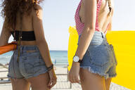 Young women with yellow airbed walking to the beach - JPTF00251