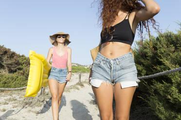 Young women walking to the beach - JPTF00254