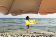 Young woman with yellow airbed at the beach - JPTF00257
