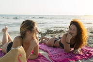 Young woman lying on towels at the beach - JPTF00263