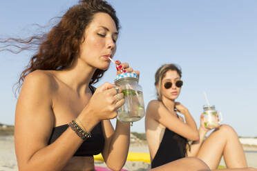 Young woman at the beach, drinking - JPTF00266