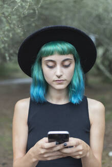 Portrait of young woman with dyed blue and green hair and nose piercing using smartphone - JPTF00275