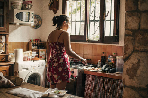 Rear view of woman cooking in kitchen - ACPF00588