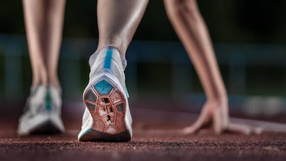 Legs of female athlete running on tartan track - STSF02193