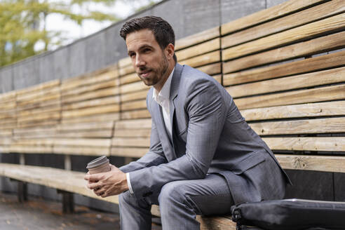 Relaxed businessman sitting on wooden bench in the city - DIGF08085