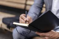 Close-up of businessman writing into notebook - DIGF08088