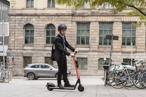 Businessman riding e-scooter in the city - DIGF08124