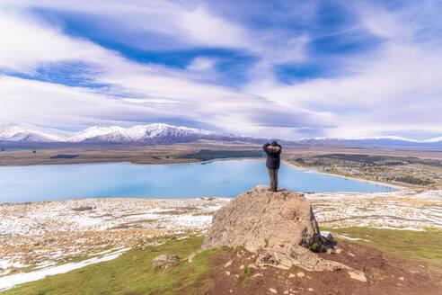 Woman enjoying view from Mount John Summit by Lake Tekapo, South Island, New Zealand - SMAF01396