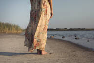 Low section of woman in a summer dress standing at a lake - MOMF00749