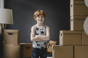 Portrait of smiling redheaded boy between cardboard boxes - KNSF06237