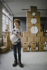 Portrait of redheaded boy with globe standing in front of rocket built of cardboard boxes - KNSF06240