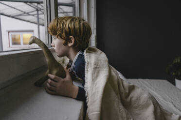 Sad boy leaning on window sill looking out of window in the evening - KNSF06243