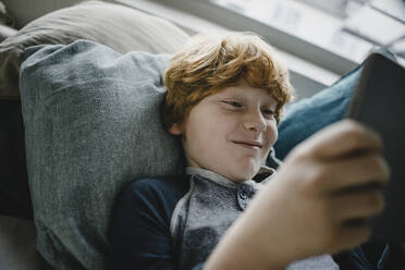 Portrait of smiling redheaded boy lying on couch using digital tablet - KNSF06249