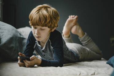 Portrait of redheaded boy lying on couch looking at mobile phone - KNSF06255