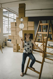 Portrait of redheaded boy playing astronaut standing in front of rocket built of cardboard boxes - KNSF06267